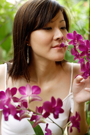 Young woman smelling orchids
