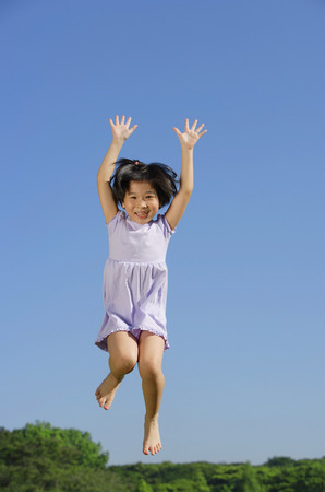 Girl jumping in mid air, arms outstretched, smiling