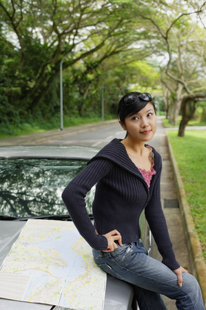 waiting glance: Woman sitting on hood of car, map next to her