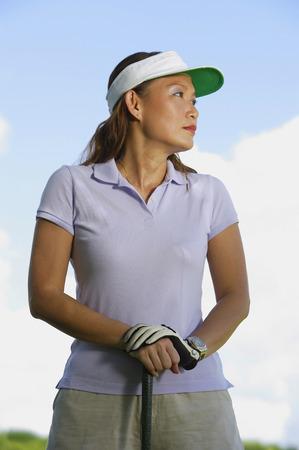 woman golf: Woman wearing sun visor, leaning on golf club, looking away