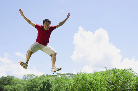mid air: Man jumping in mid air, arms outstretched LANG_EVOIMAGES