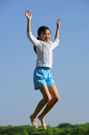 mid air: Girl jumping in mid air, smiling at camera LANG_EVOIMAGES