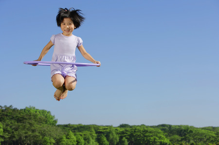 mid air: Girl jumping in mid air, holding plastic hoop LANG_EVOIMAGES