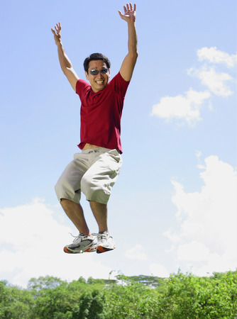 mid air: Man jumping in mid air, arms outstretched, smiling LANG_EVOIMAGES