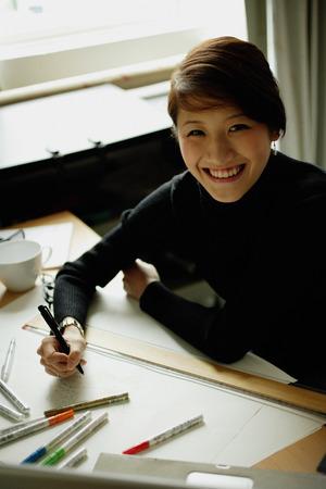 felt tip: Female designer sitting at table with ruler and felt tip marker, smiling at camera
