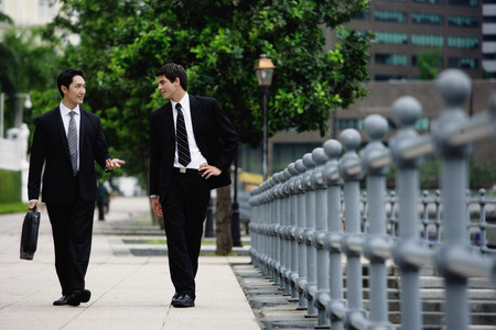 Two businessmen walking and talking LANG_EVOIMAGES