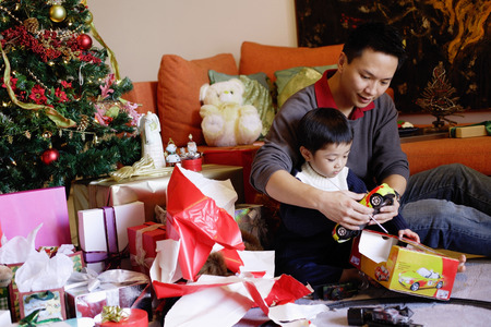 Father and son opening gifts on Christmas, portrait