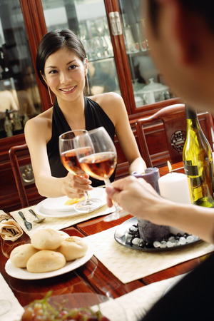 toasting wine: Man and woman toasting wine glasses across dining table