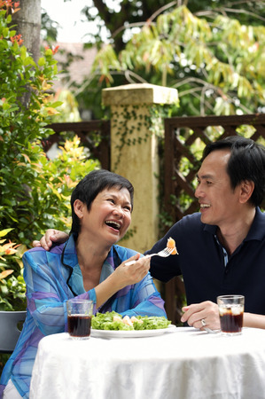 Mature couple laughing while dining in restaurant LANG_EVOIMAGES