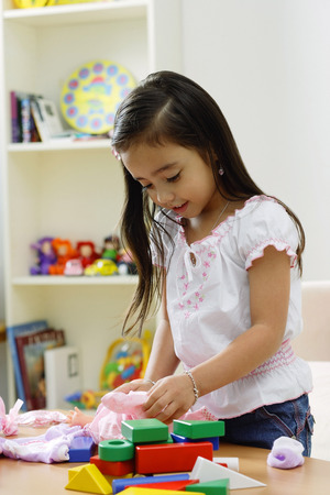 look pleased: Young girl playing with toys