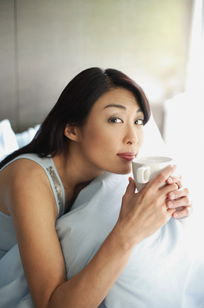 Woman sitting on bed, holding cup to lips, looking at camera