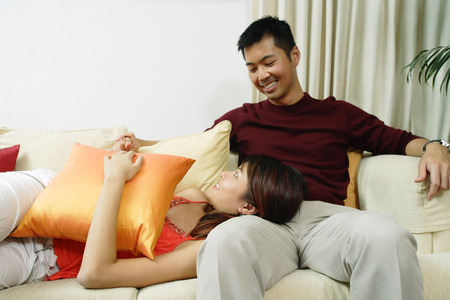 Couple in living room, woman lying on mans lap Stockfoto