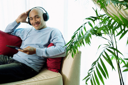 Man on sofa with headphones, listening to music, smiling at camera