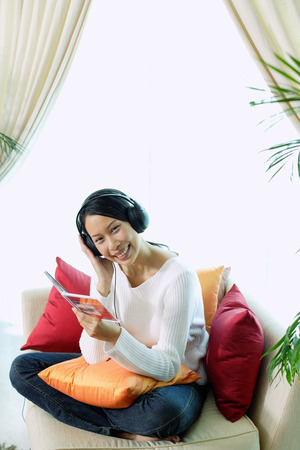 Woman sitting on sofa, wearing headphones, smiling at camera, portrait LANG_EVOIMAGES