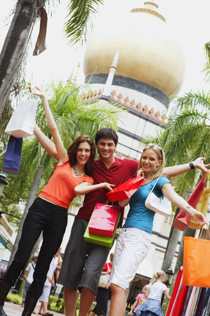 Three tourists posing for camera, mosque in the background