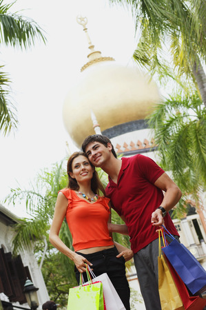 Couple standing side by side, mosque in the background