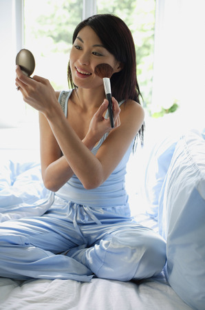 Woman sitting on bed, holding compact, applying make-up Stock Photo