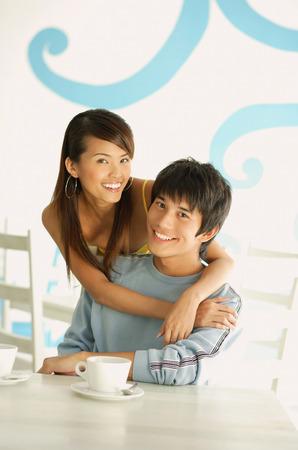 seated man: Mujer que abraza a hombre asentado, ambos sonriendo a la cámara LANG_EVOIMAGES