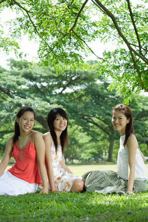 Young women sitting on grass, smiling at camera LANG_EVOIMAGES