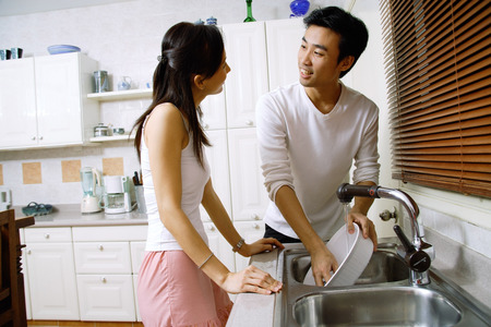 Couple in kitchen, washing dishes