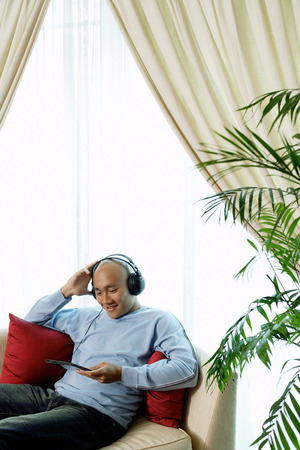 Man on sofa with headphones, listening to music