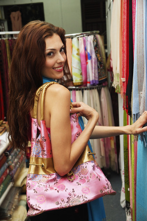 over the shoulder: Woman in clothes shop, looking over shoulder at camera LANG_EVOIMAGES
