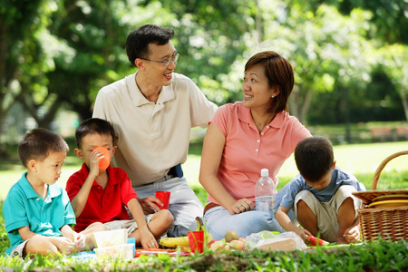 Family with three boys having picnic in park