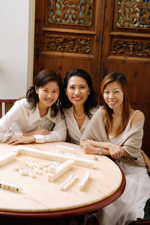 Three women sitting next to each other, at mahjong table, smiling Stock Photo