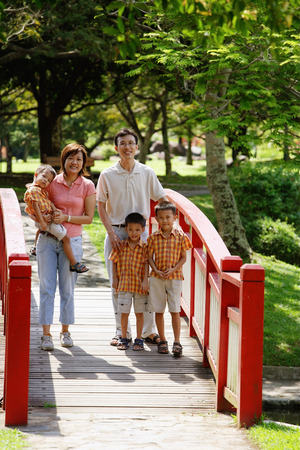 Family with three boys in park, standing on bridge, smiling at camera LANG_EVOIMAGES