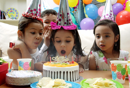 Birthday party, young girl blowing candles on cake