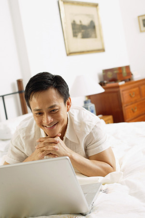 chin on hands: Man in bedroom, looking at laptop, hands clasped, under chin
