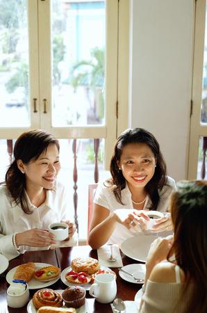 Three women having tea at cafe, high angle view