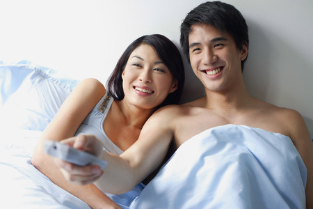 Couple sitting up in bed, watching TV, man holding TV remote control