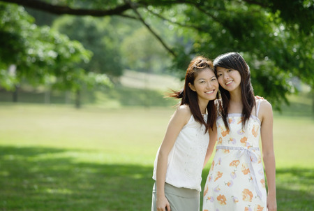 people: Two young women standing side by side, cheek to cheek