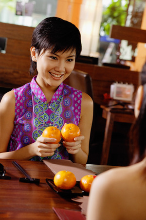 Young woman holding two oranges, smiling at person in front of her