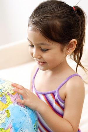 Girl looking down at globe