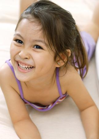 girl lying down: Young girl, lying down, smiling