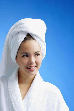 woman bathrobe: Young woman wearing white bathrobe and towel turban, head shot