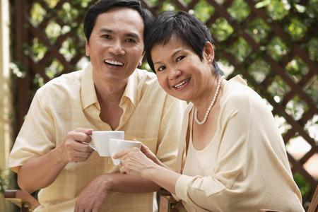 potěšen: Mature couple smiling at camera while having tea