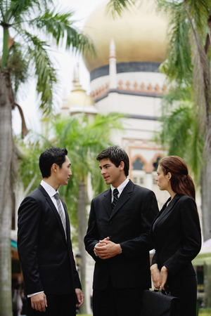 together with long tie: Two businessmen and one businesswoman standing, having a discussion, mosque in the background