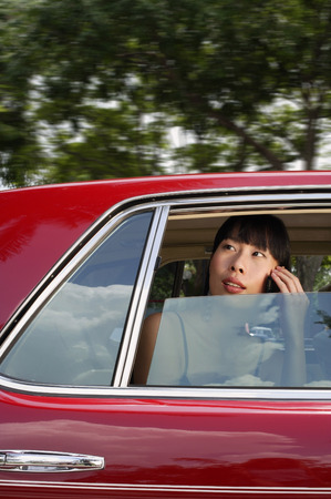 Woman sitting in car, using mobile phone, looking through the window LANG_EVOIMAGES