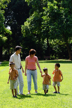 Family with three boys walking in park