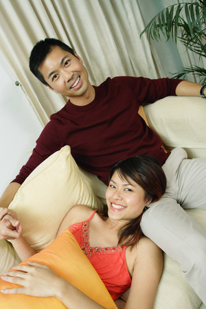 pantalones abajo: Couple in living room, woman lying on mans lap, smiling at camera
