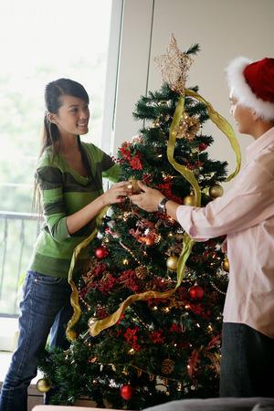 decorating: Couple decorating Christmas tree
