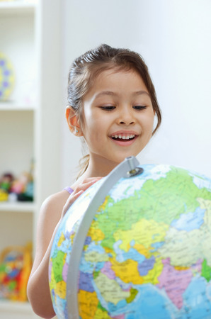Young girl looking at globe, big smile LANG_EVOIMAGES