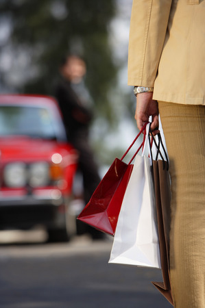 cropped: Woman carrying shopping bags, cropped image