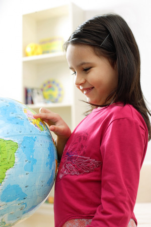 Young girl standing and looking at globe LANG_EVOIMAGES