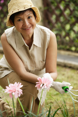 only 1 person: Woman doing gardening while smiling at camera