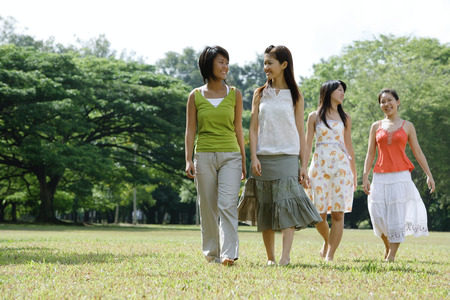 Four young women walking across field