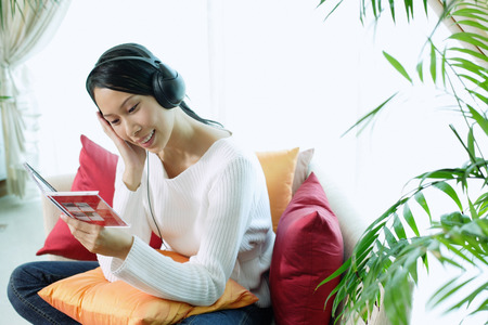 Woman sitting on sofa, wearing headphones LANG_EVOIMAGES